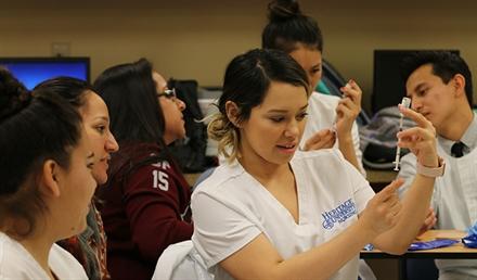 Nursing student looking at syringe