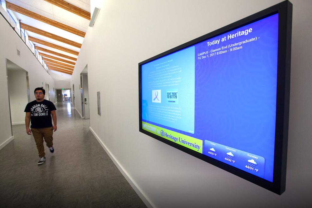 Student walking down educational building hallway