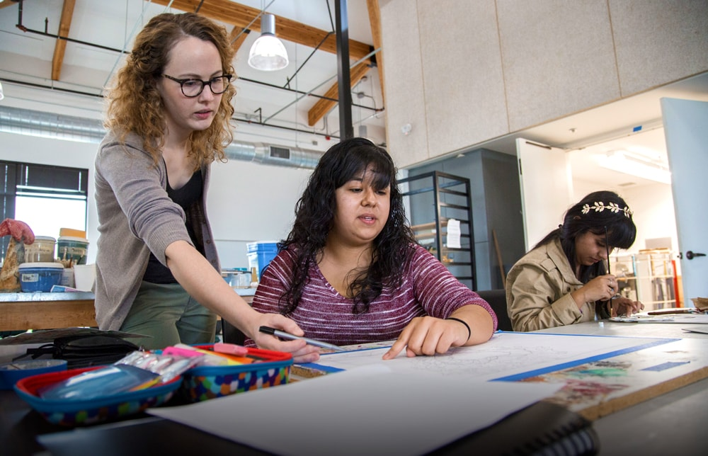 Arts professor advising student over her shoulder