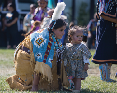 Native American teen and child dressed in native clothes