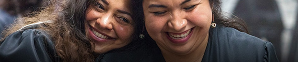 Two female students happy, smiling during graduation ceremony