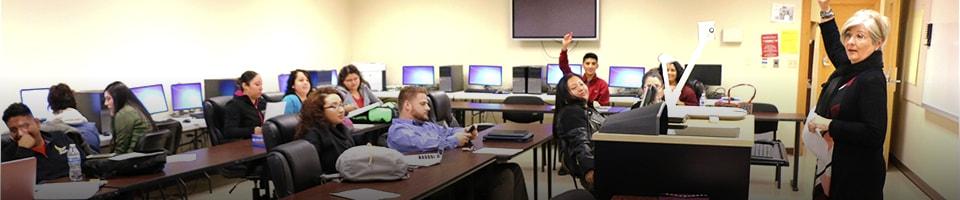 Students in classroom raising hand teacher