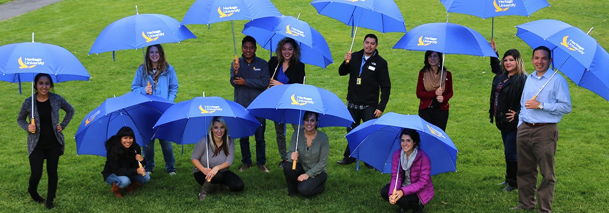 Heritage University group of teachers and students posing outside with blue umbrellas