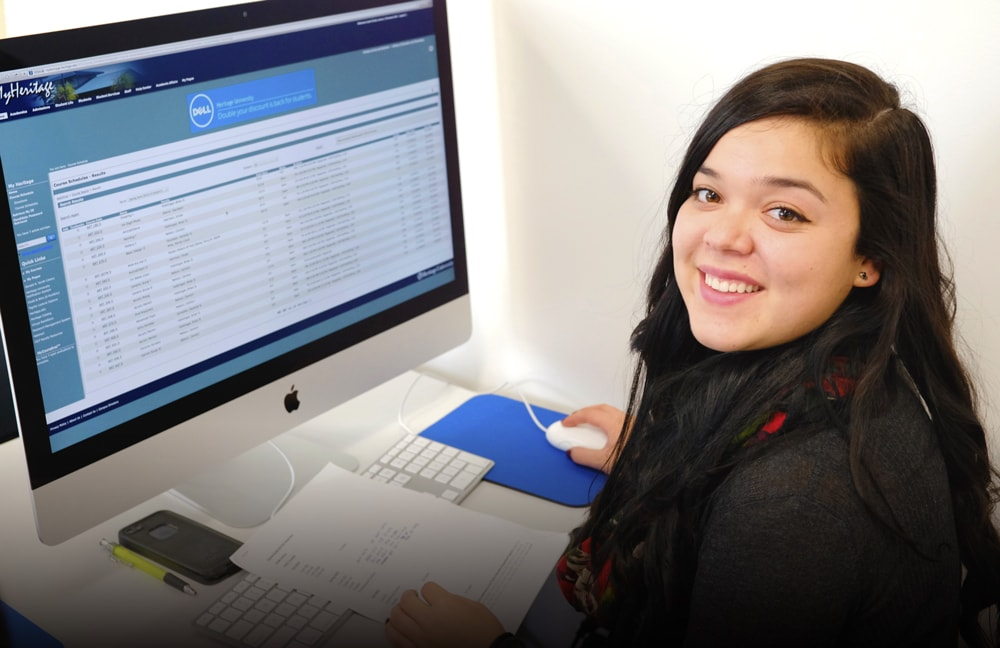 Female student sitting in front of computer smiling at camera