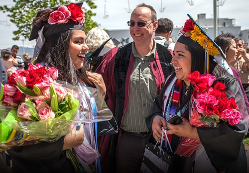 Students laughing with flowers celebrating graduating
