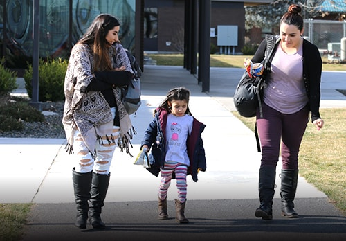 Female students with kid walking on campus