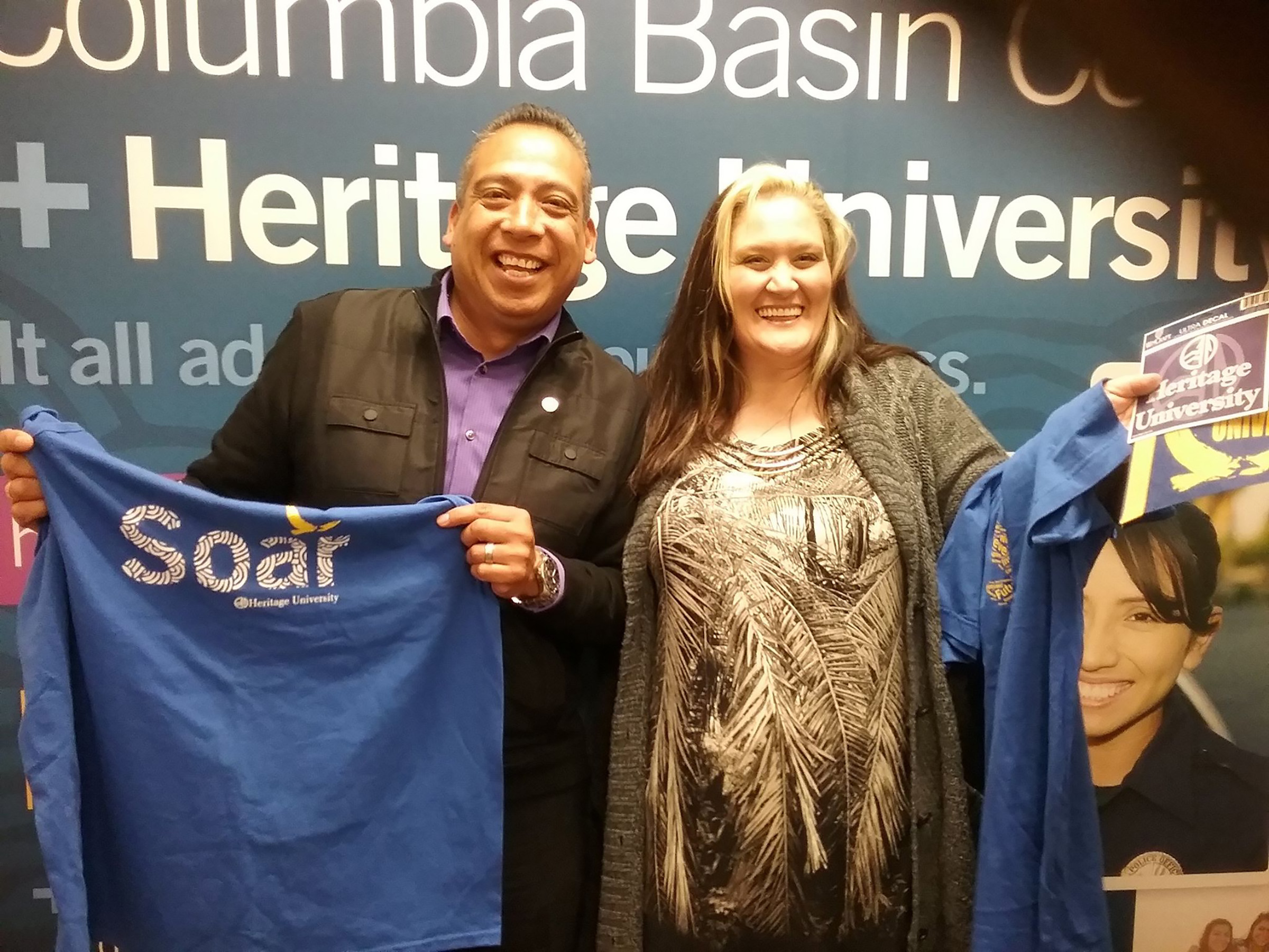 Miguel Juarez and a college hold up Heritage University T-shirts at Heritage's regional branch at Columbia Basin College in Pasco, Wash.