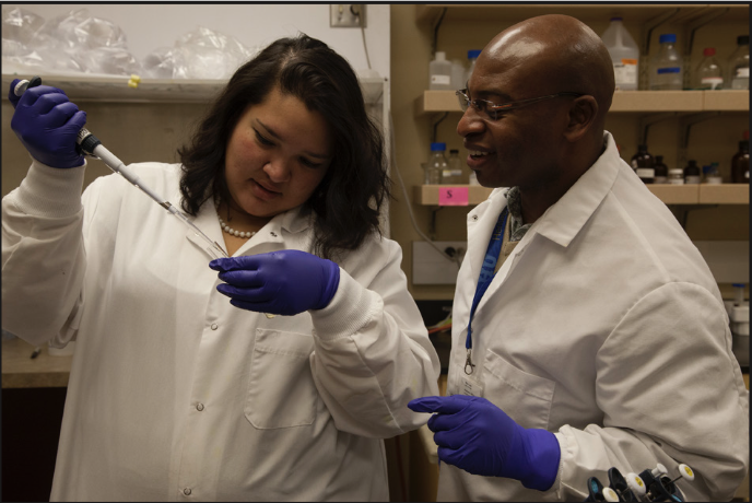Melvin Simoyi watches his student fill a beaker during a lab class at Heritage University