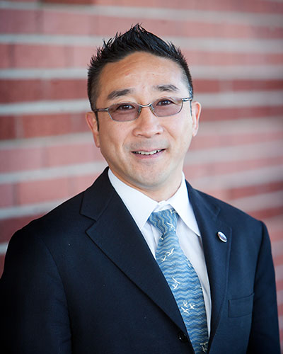 Portrait photo of Kazuhiro Sonoda, who is standing in front of a brick wall