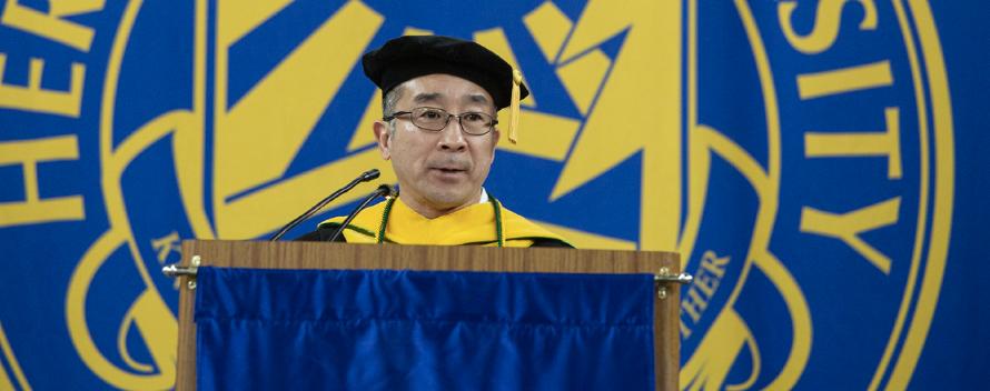 Kazuhiro Sonoda standing at a podium during an undated Heritage University commencement ceremony