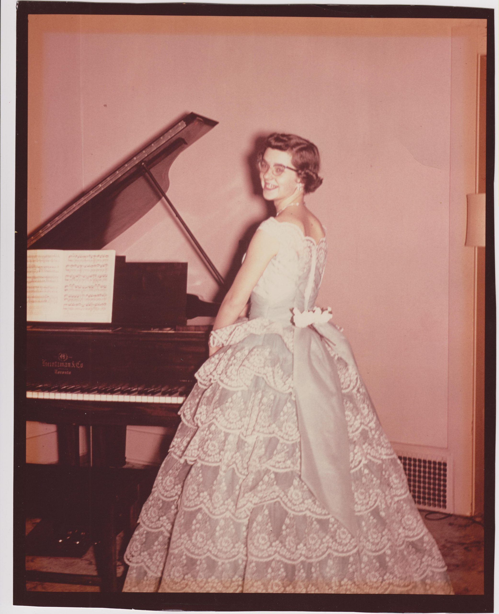 Kathleen Ross, snjm before a piano recital, 1958 standing next to a piano wearing a white dress