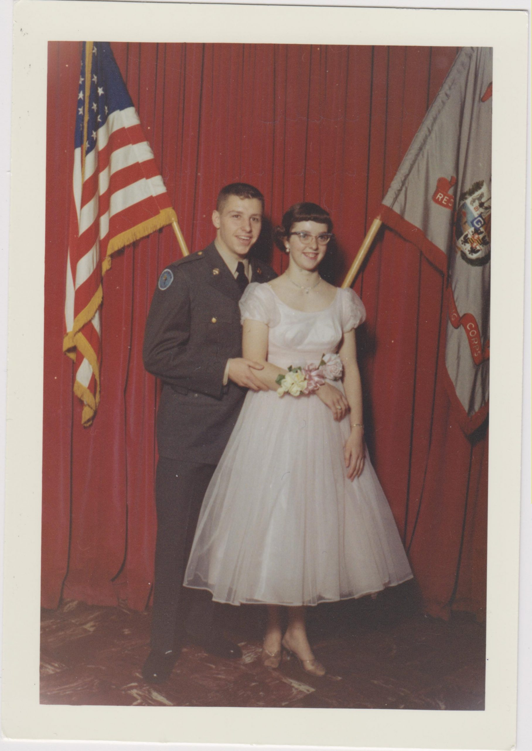 Kathleen Ross, snjm in a white dress posing with a young man dressed in a military uniform