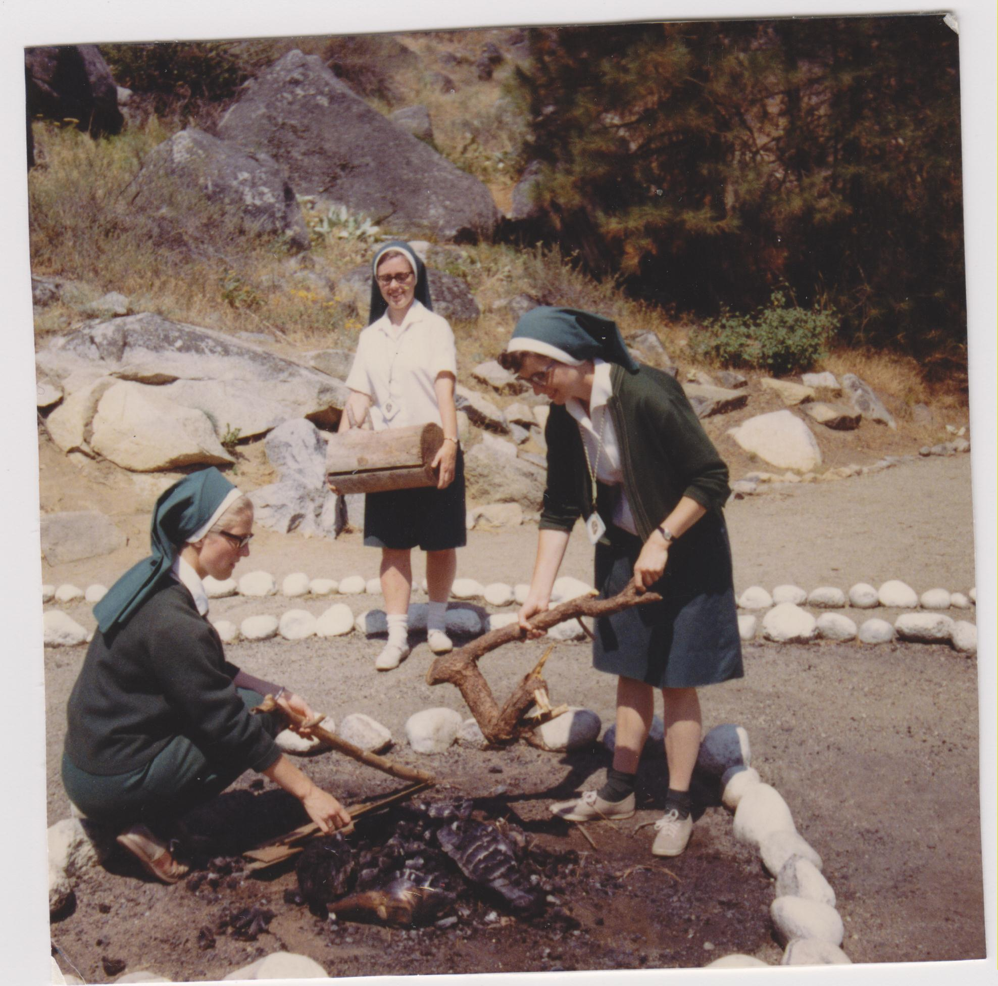 Kathleen Ross, snjm with two Sisters at an extinguished campfire, 1968