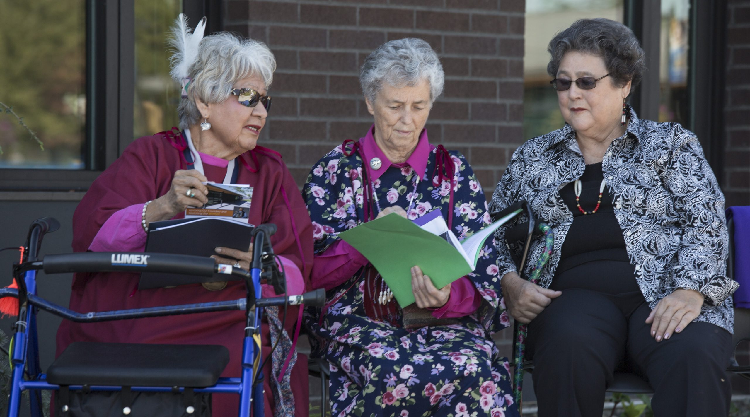Kathleen Ross, snjm at the dedication of the Martha B. Yallup Health Sciences Building at Heritage University, holding a green folder with Martha Yallup at her left and Yallup's sister to her right.
