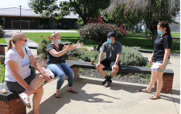 Heritage University students sit outside the Kathleen Ross, snjm Center during the beginning of the fall 2020 semester